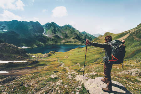 Hiker Man enjoying lake and mountains view with backpack Travel Lifestyle motivation concept adventure vacations outdoor photo