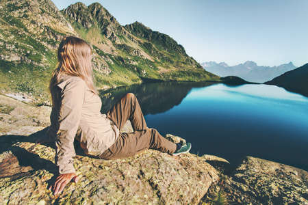 Jonge vrouw ontspannen op het meer in de bergen Reizen Lifestyle wanderlust concept zomervakantie outdoor harmonie met de natuur Stockfoto