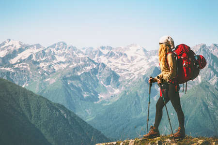 Woman Traveler standing on mountain cliff with red backpack Travel Lifestyle concept adventure summer vacations outdoor wild nature landscape photo