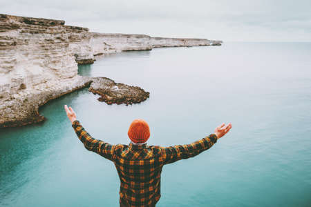 Man enjoying cold sea view alone raised hands Travel Lifestyle concept adventure vacations outdoor. Stylish guy wearing fashion orange knitted hat happiness emotions