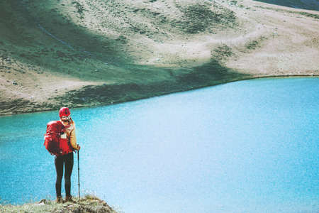 Woman backpacker on cliff over lake in mountains Travel Lifestyle adventure wanderlust concept summer vacations hiking outdoor