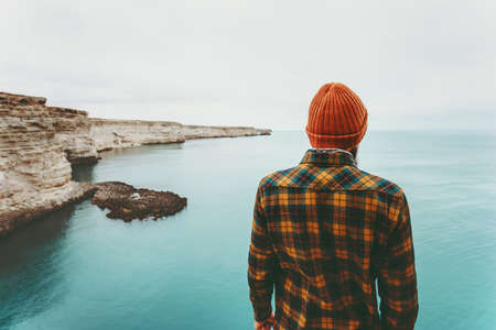 Man enjoying view of cold sea Travel Fashion Lifestyle orange hat and cozy shirt clothing harmony with nature authentic style concept