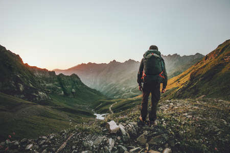 Man hiking at sunset mountains with heavy backpack Travel Lifestyle wanderlust adventure concept summer vacations outdoor alone into the wild 版權商用圖片