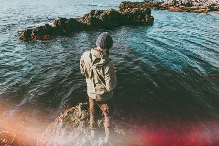 Man traveler walking at cold sea alone Travel Lifestyle concept adventure vacations outdoor natural sun lighting effect Stock Photo