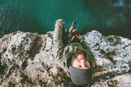 Happy Man traveler relaxing on cliff above cold sea Travel Lifestyle concept vacations outdoor positive emotions aerial view