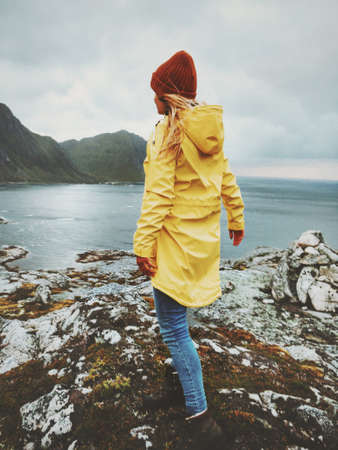 Woman walking in Norway mountains above fjord Travel Lifestyle concept adventure vacations outdoor. Girl wearing fashion yellow raincoat and hat autumn season Stock Photo