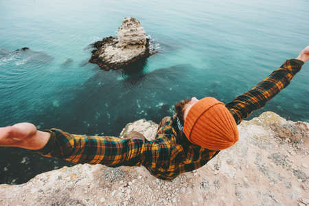 Man traveler hands raised sitting on cliff above sea aerial view Travel Lifestyle concept adventure vacations outdoor happiness success emotions Stock Photo