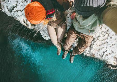 崖の上に一緒に座っている愛の男と女性のカップル旅行幸せな感情ライフスタイルの概念。ロマンチックな休暇秋の冬のシーズンの空中写真を旅行 写真素材