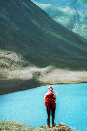 Backpacker girl standing on cliff over lake in mountains Travel Lifestyle adventure concept summer vacations outdoor exploring wild nature