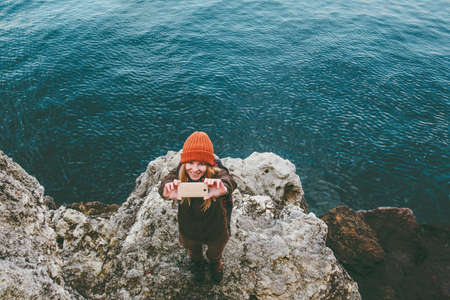 Young Woman taking selfie photo by smartphone Travel Lifestyle concept adventure vacations at sea winter beach outdoor