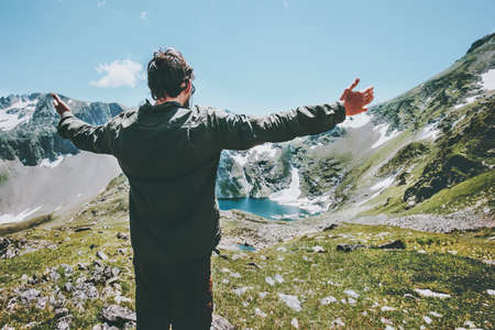 Man hands raised enjoying landscape mountains and lake Travel Lifestyle adventure concept summer vacations outdoor exploring wild nature