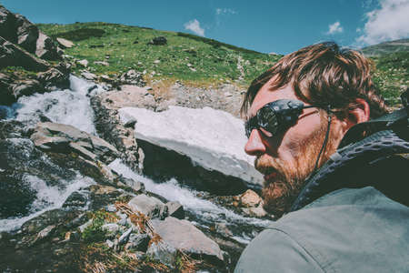 Bearded Man wearing mountain sunglasses hiking Travel Lifestyle concept adventure  vacations survival outdoor