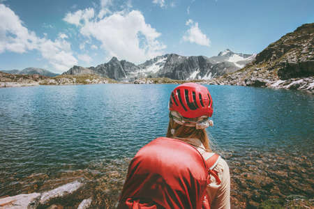 Hiker trekking at blue lake in mountains Travel Lifestyle adventure concept summer vacations outdoor exploring wild nature wearing helmet
