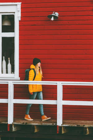 Traveler woman walking in Norway village red house wall on background Travel Lifestyle concept winter vacations outdoor