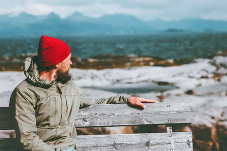 Man sitting on bench enjoying sea and mountains landscape Traveling alone Lifestyle emotions concept