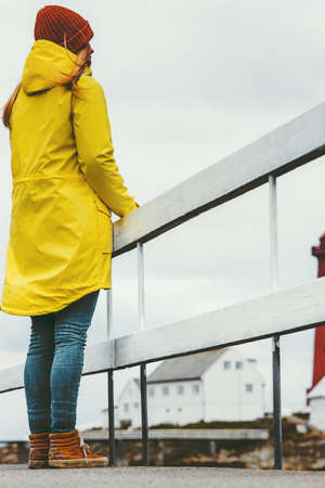 Woman in yellow raincoat enjoying Norway landscape Travel Lifestyle concept adventure winter vacations outdoor