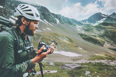 Traveler Man photographer with backpack hiking in mountains Travel Lifestyle adventure concept summer vacations outdoor exploring wild nature wearing helmet Stockfoto