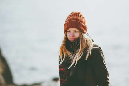 Woman at winter beach cold sea outdoor wearing hat and scarf sad depression emotions Lifestyle autumn seasonal concept Stockfoto