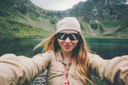 Woman traveler taking selfie hiking in mountains Travel Lifestyle adventure concept active summer vacations outdoor