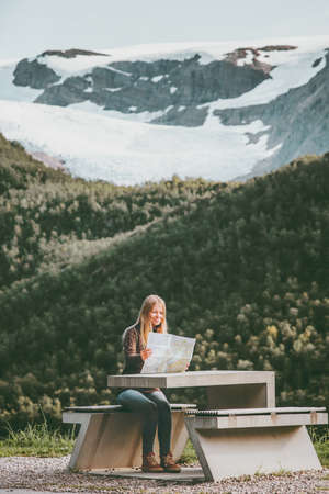 Young Woman tourist with map planning route trip in Norway sitting at the table Travel Lifestyle concept adventure vacations outdoor Svartisen glacier on background