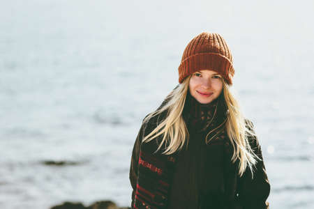 Young Woman smiling walking at winter sea Travel Fashion Lifestyle concept outdoor. Girl wearing orange hat and scarf cold weather Stockfoto