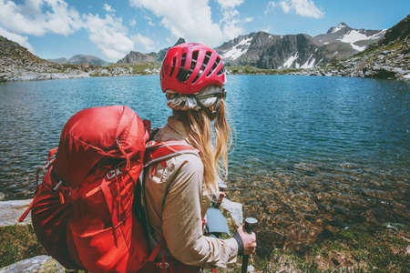 Backpacker girl hiking at blue lake in mountains with red backpack Travel Lifestyle adventure concept summer vacations outdoor exploring wild nature