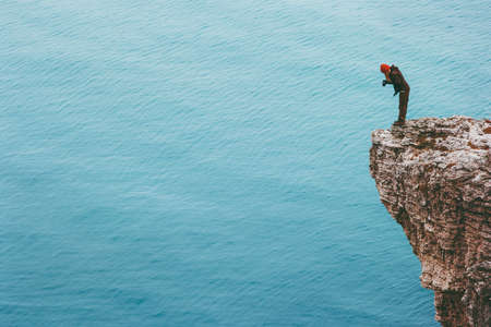 Traveler photographer on cliff above sea Travel Lifestyle concept adventure active vacations outdoor