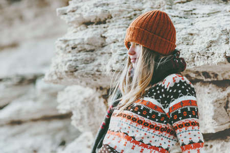 Girl relaxing alone at rocky seaside Travel Lifestyle fashion concept winter vacations outdoor