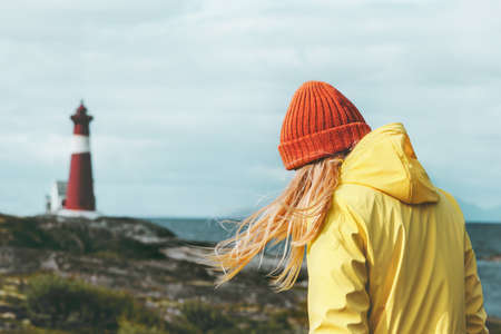 Traveler girl walking at Norway lighthouse sea landscape Travel Lifestyle concept adventure scandinavian vacations outdoor Stock Photo