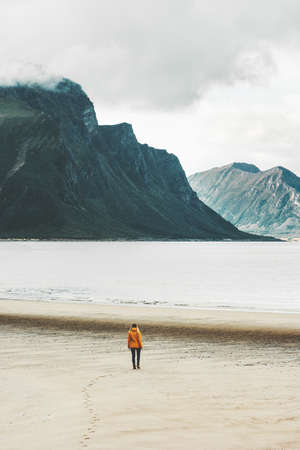 Traveler walking alone at sea sandy beach in Norway Travel Lifestyle concept adventure scandinavian vacations outdoor harmony with nature Stock Photo
