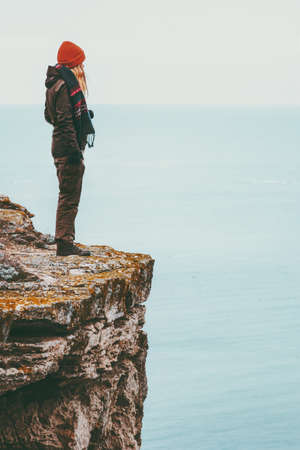 Woman alone standing on cliff edge above sea Travel Lifestyle concept Solitude melancholy emotions harmony with nature