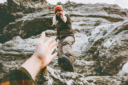 Couple Man and Woman help giving hands climbing mountains Love and Travel Lifestyle concept. Young family hiking adventure vacations outdoor