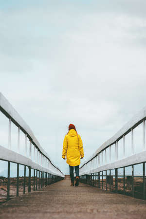 Girl Traveler alone walking away on bridge road Travel Lifestyle emotional concept vacations outdoor yellow raincoat clothing Banque d'images