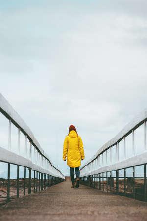 Girl Traveler alone walking away on bridge road Travel Lifestyle emotional concept vacations outdoor yellow raincoat clothing Stockfoto