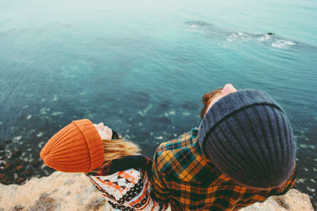 Couple in love Man and Woman together above sea on cliff looking up Traveling happy emotions Lifestyle concept. Young family at romantic vacations autumn winter season aerial view