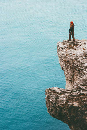 Traveler standing on cliff over cold sea alone Travel Lifestyle concept outdoor. Solitude melancholy emotions