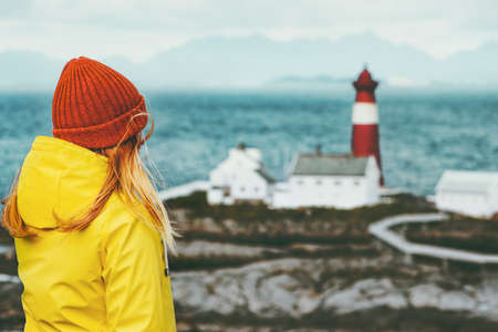 Young woman enjoying Norway lighthouse sea landscape Travel Lifestyle concept adventure scandinavian vacations outdoor Stockfoto