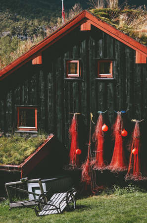 Traditional fishing house with grass on roof and mountains landscape on background  in Norway