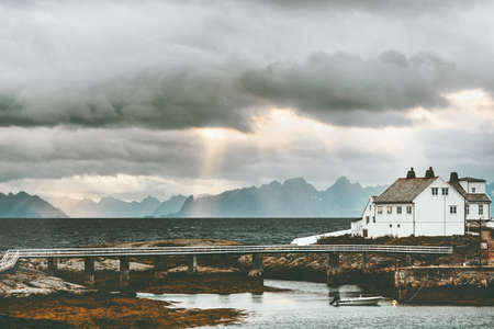 Norway Landscape white traditional house at sunset sea and mountains on background Travel scenery