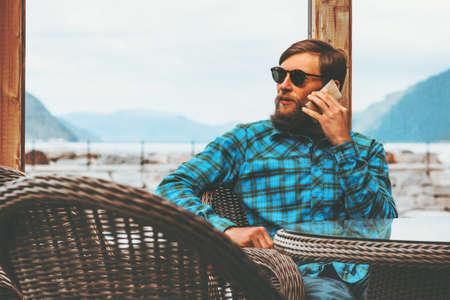 Bearded Man talking by smartphone modern Lifestyle success technology concept businessman sitting near window Stockfoto
