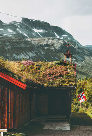 Traditional norwegian house with grass on roof and mountains landscape on background  in Norway