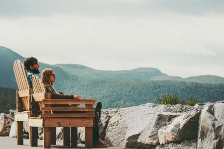 Couple in love Man and Woman relaxing together outdoor Travel Lifestyle concept family sitting on wooden chairs