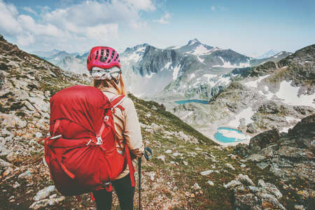 Adventurer tourist hiking in mountains with backpack Travel Lifestyle hiking adventure concept summer vacations outdoor exploring wild nature