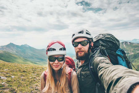 Couple hikers Man and Woman together taking selfie climbing in mountains Travel Lifestyle concept tourists wearing helmet gear Stockfoto