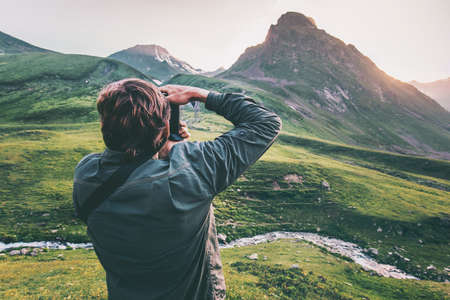 Man blogger photographer taking photo of sunset mountains Travel Lifestyle hobby concept adventure active vacations outdoor Stockfoto