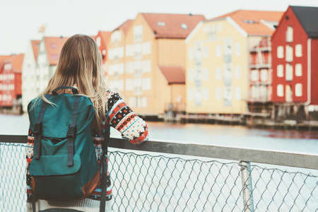 Tourist woman with backpack sightseeing walk in Trondheim city Norway vacations weekend Travel Lifestyle fashion outdoor scandinavian houses landmarks architecture on background Stockfoto