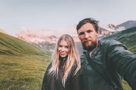 Couple in love Man and Woman together taking selfie in mountains Travel Lifestyle concept tourists at romantic vacations