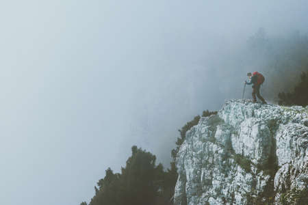 Traveler on foggy cliff mountains with backpack Travel Lifestyle success motivation concept adventure active vacations outdoor Stockfoto