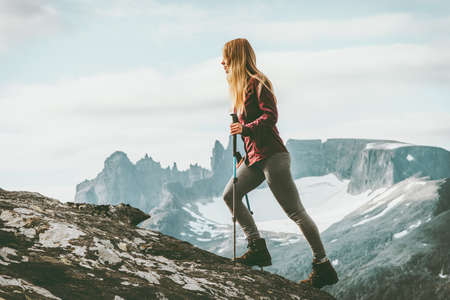 Woman adventurer hiking in Norway mountains Travel healthy lifestyle concept active weekend summer vacations