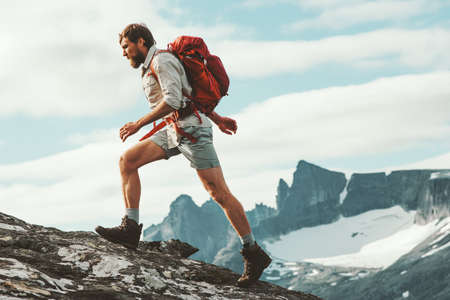 Man trail running in mountains with backpack Norway Travel hiking lifestyle concept active weekend summer vacations wild trek